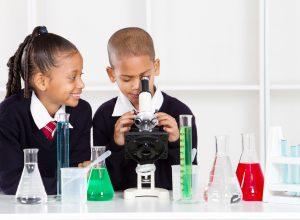 elementary school kids in science class using a microscope