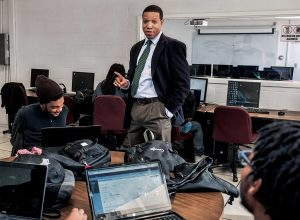 A Black teacher talking to Black coders