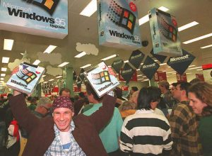 A White man holding two copies of Windows 95 in his hands