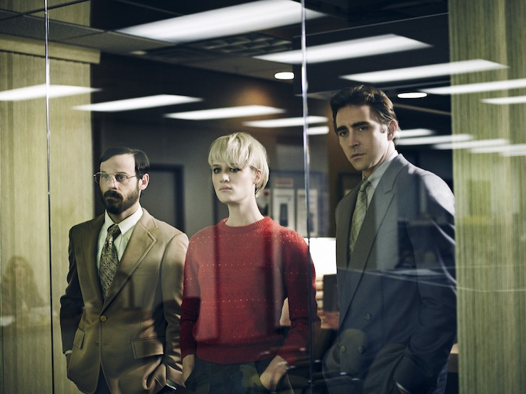 Two men and a woman look through a glass office window